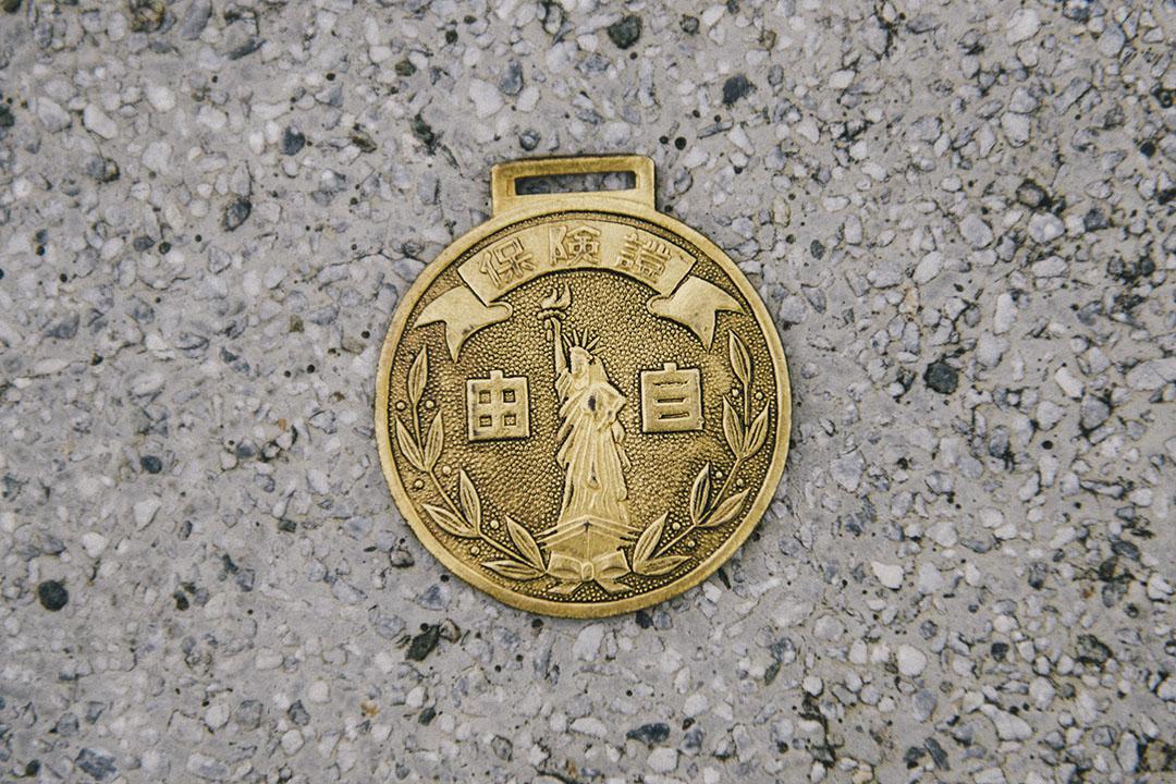 吳明益的老鐵馬局部細節,與他所收藏的早期腳踏車車牌、保險牌。攝:趙豫中/端傳媒