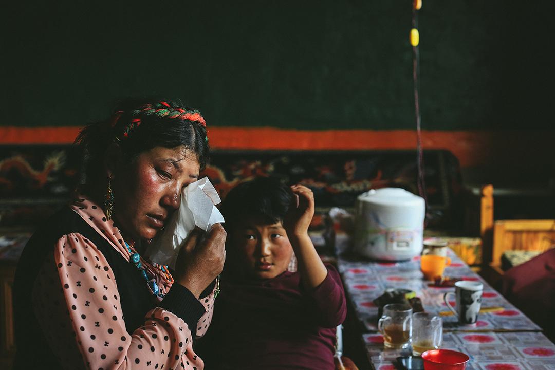 索加鄉移民村村民想起在地震中失去的親人不禁落淚。攝 : 王嘉豪/端傳媒