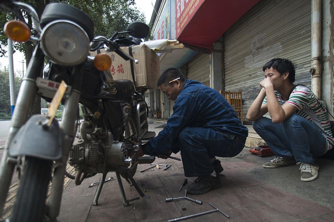 馮世康(中)在攀成鋼老廠區門口開了一間修車鋪,攀成鋼關停後,他的生意大不如前。攝:Yue Wu/端傳媒