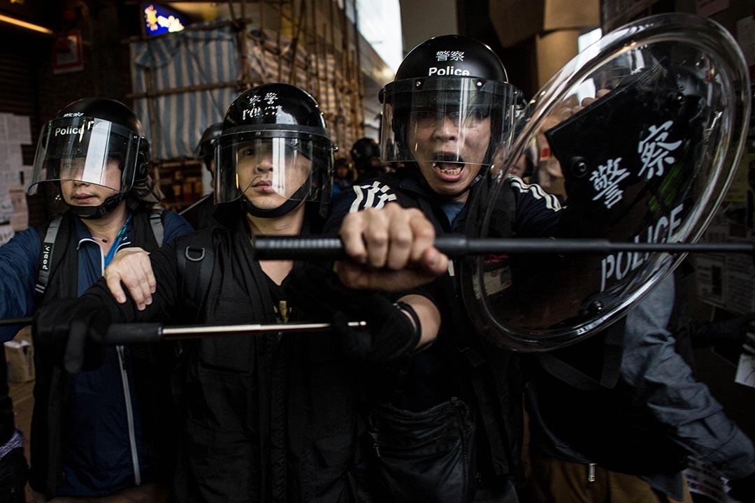 2014年12月1日,香港金鐘,防暴警察在雨傘運動佔領區附近的地鐵站軀趕示威者。攝:Chris McGrath/GETTY