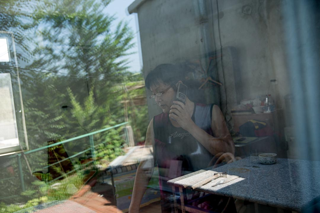 在北京西郊的月亮灣救助站,張玉芬正在接聽諮詢電話。攝: Jason Jia/端傳媒