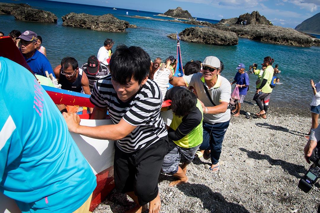 划船比賽結束,夏曼·藍波安(戴墨鏡者)開心地與眾人一同迎接歸來的紅頭部落大船。攝: 王文彥/端傳媒