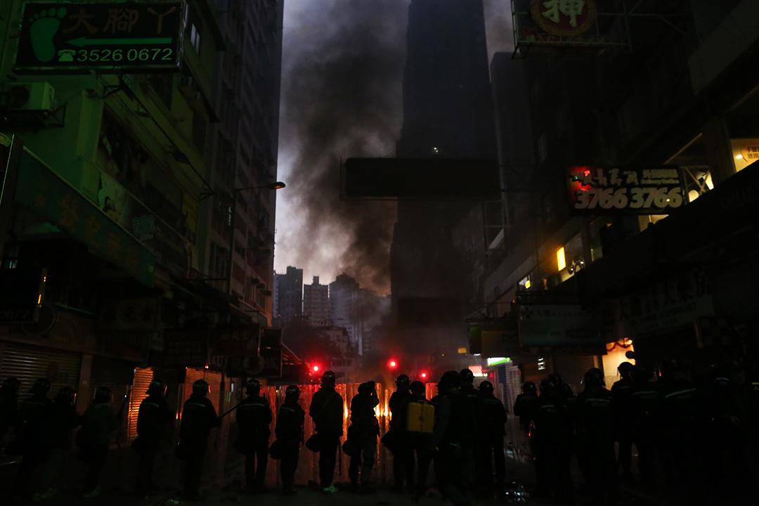 2016年2月9日清晨約七時,示威者在旺角街道焚燒雜物,防暴警察持盾戒備。攝:盧翊銘/端傳媒
