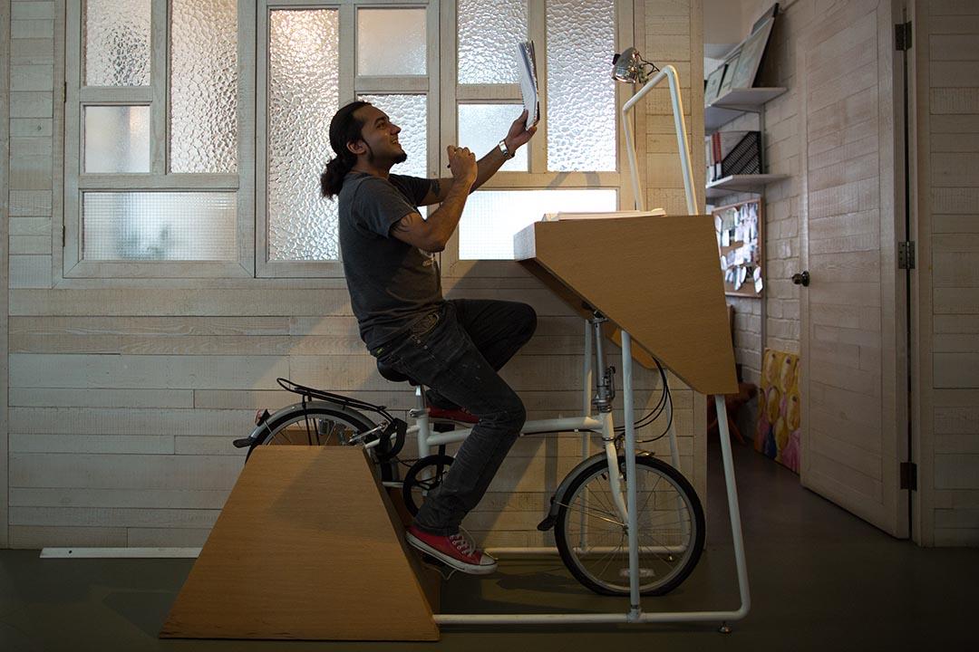 設計師譚家坤把辦公室佈置得輕鬆溫馨,設有單車式寫字枱,有年輕員工兩腳邊踩,邊自拍,邊看文件。攝:盧翊銘/端傳媒