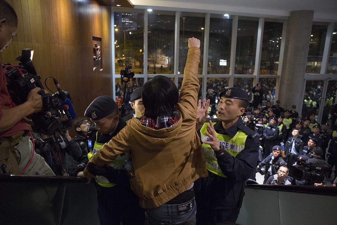2016年3月11日,香港,立法會財務委員會以舉手投票通過追加高鐵撥款後,有示威者在立法會大堂示威。其中一名示威者、社會民主連線副主席黃浩銘被警察帶走前振臂喊口號。攝:羅國輝/端傳媒