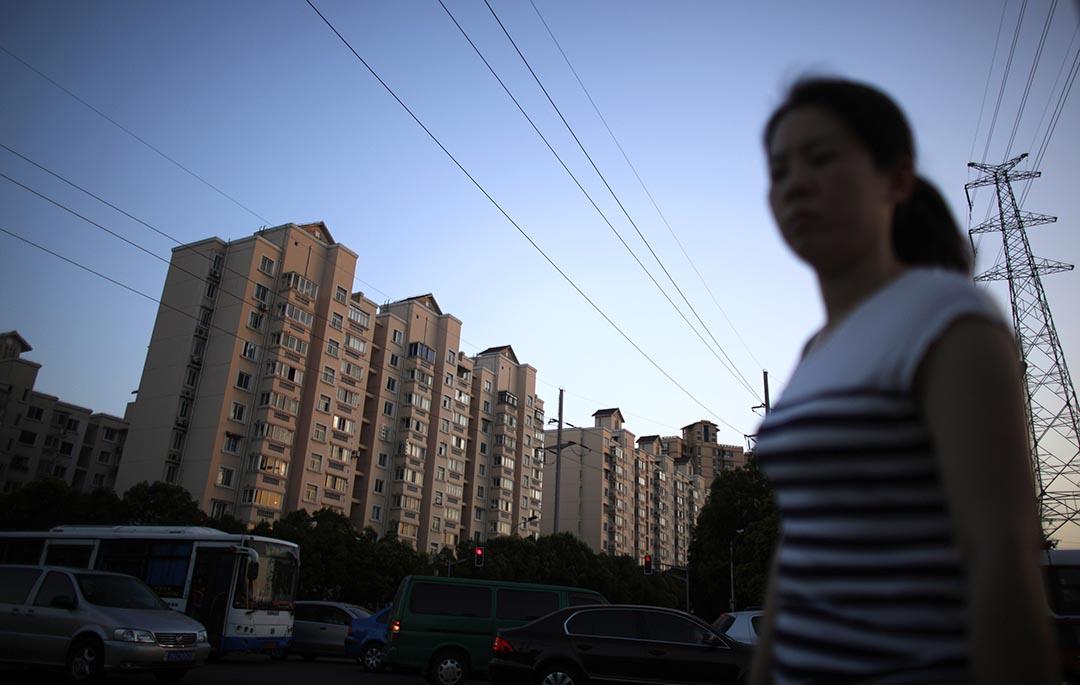 中國央行和銀監會聯合發布措施,除限購城市外,城市居民首次購買個人住房最低首付比由30%下調為25%。圖為一名女子走過上海浦東區住宅區。攝:Carlos Barria/REUTERS