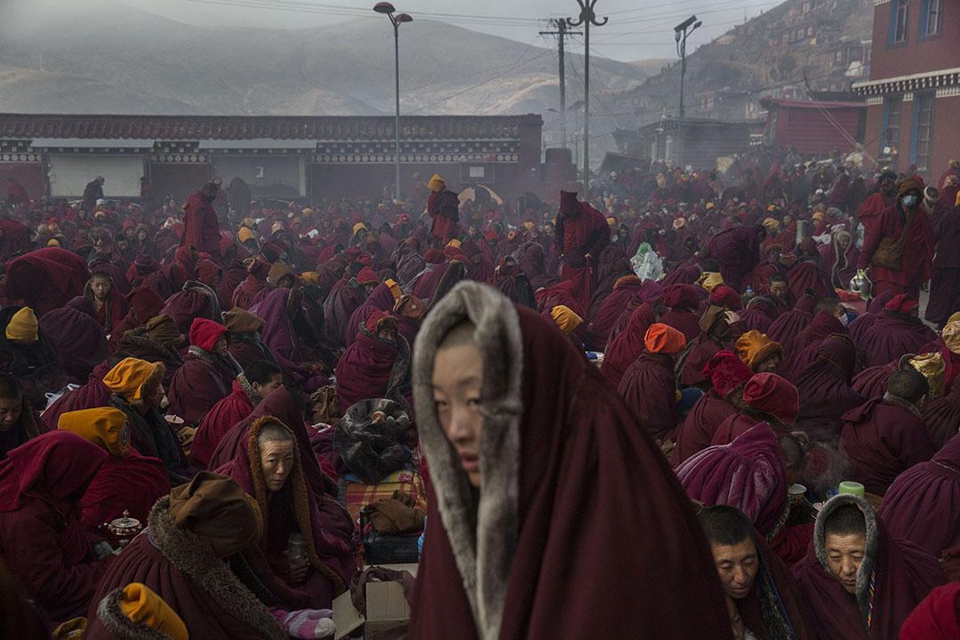 天氣寒冷,喇嘛們披著厚厚的上衣,在佛學院裡坐著。攝:Kevin Frayer/Getty Images