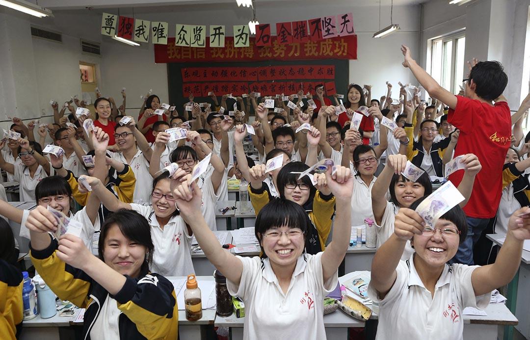 學生舉起老師給予寓意考試幸運的紙幣合照。圖為一間河北省學校的學生在舉行的全國高考前,參與一個增加士氣的活動。攝 : Stringer/REUTERS