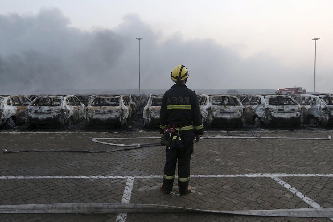 一名消防員站在天津濱海新區爆炸中受損的車輛前。