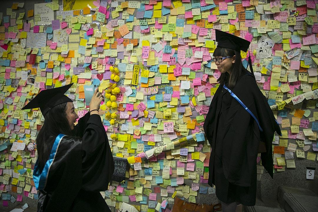 理工大學畢業生於去年雨傘運動期間在金鐘佔領區「連儂牆」前拍照留念。攝: Paula Bronstein/Getty