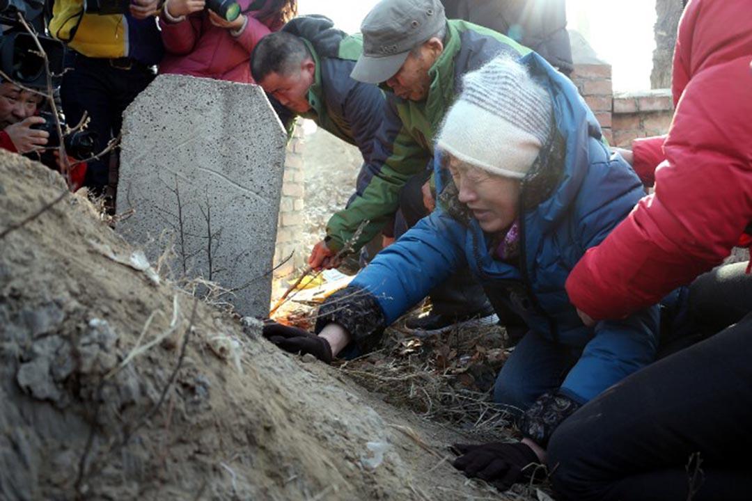 2014年12月15日,內蒙古自治區高院再審判決,呼格吉勒圖無罪,呼格吉勒圖的母親在呼格墳前痛哭。攝:TIAN ZHONGYU / IMAGINECHINA/ AFP