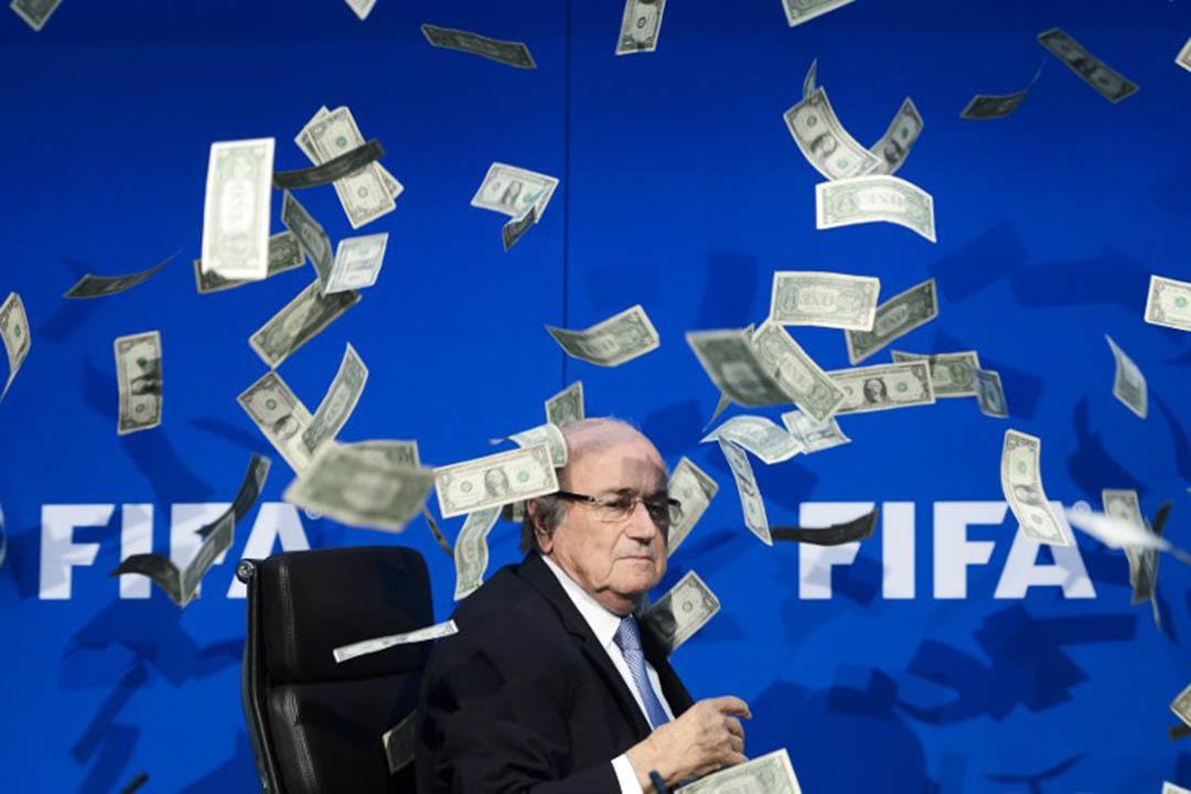 2015年7月20日,白禮達出席國際足協於舉行執委會會議後記者會,一位英國喜劇演員Simon Brodkin向其拋假銀紙諷刺其貪污醜聞。攝:FABRICE COFFRINI/AFP