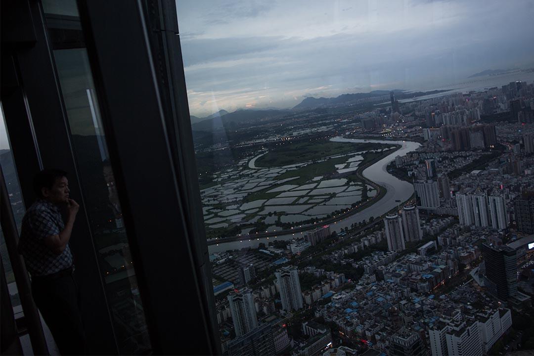 一名男子在觀賞中港兩地邊界的景色。攝:盧翊銘/端傳媒