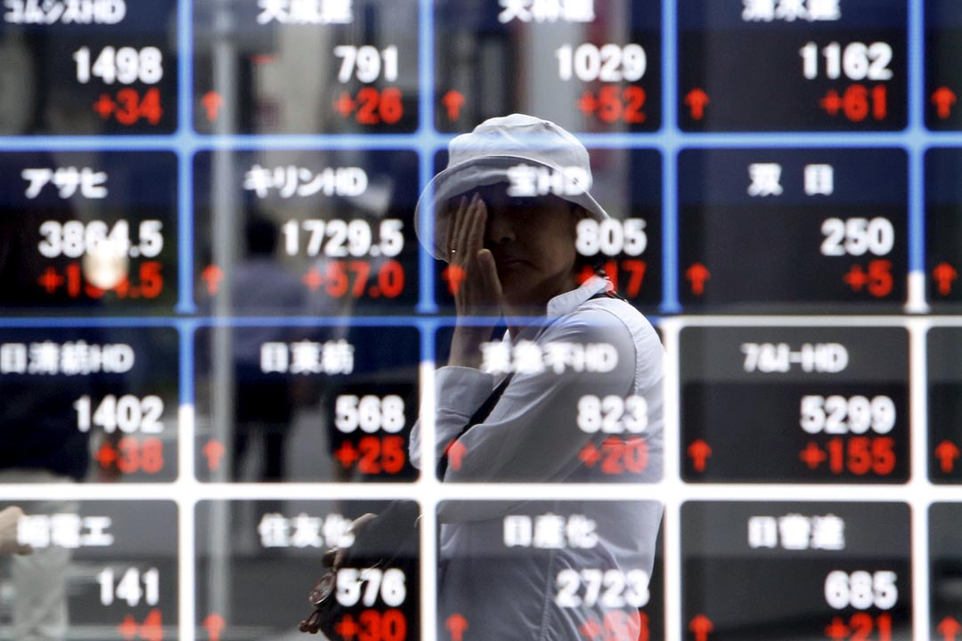 關焯照:兩個大經濟體,包括歐元區和日本,為了挽救長期低迷的經濟,也仿效美國分別推出量寬,這無疑令金融市場火上加油。圖為一名女士在日本東京的股票電子顯示屏前走過。攝:Yuya Shino/REUTERS