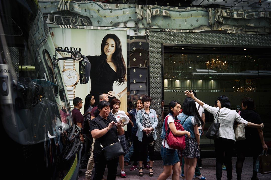 紅磡民樂街發生「苗春起」事件後,街道上的定點購物商鋪依舊正常營業,大批旅客乘大巴抵達。攝:葉家豪/端傳媒