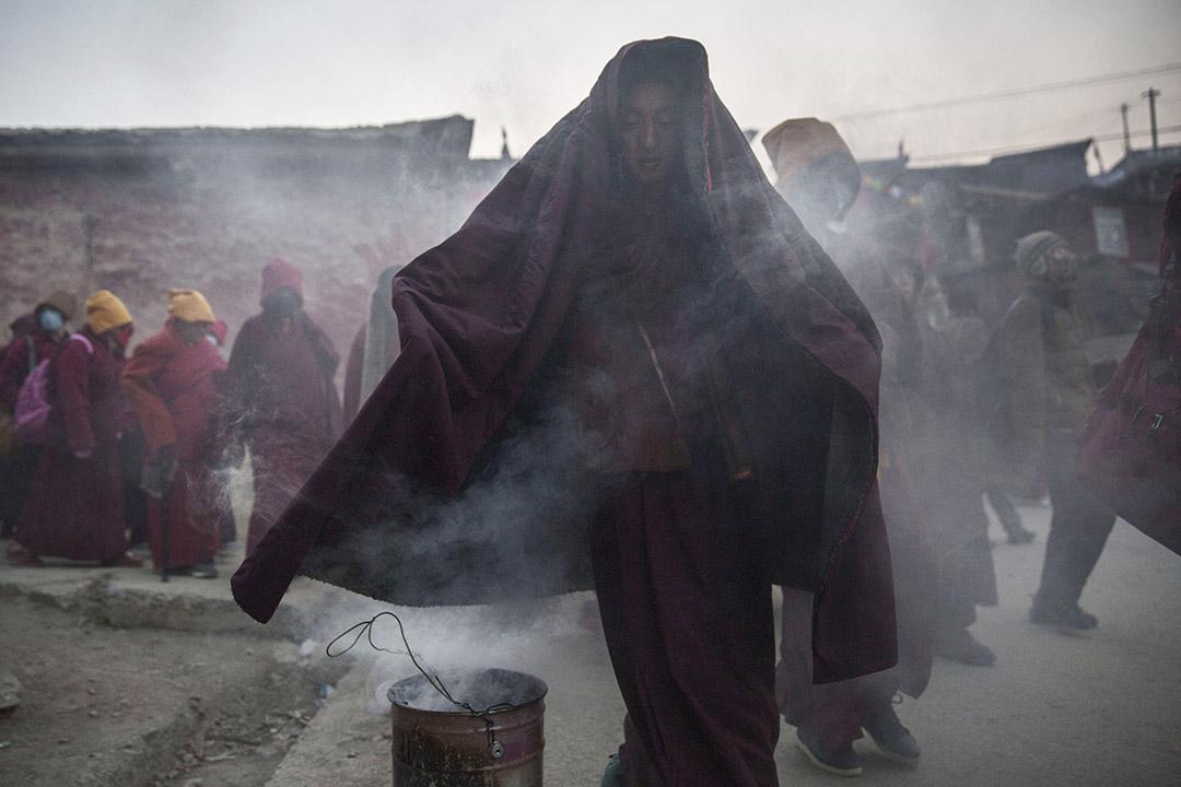 10月31日早上,色達喇榮五明佛學院,一名喇嘛在煙霧中穿過。攝:Kevin Frayer/Getty Images