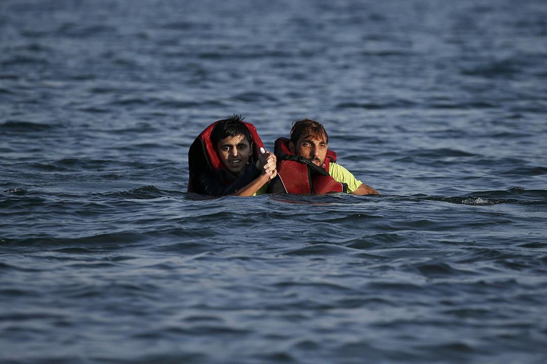 一名敘利亞難民在海上協助另一名難民,他們偷渡的橡皮艇在前往希臘途中沉沒。