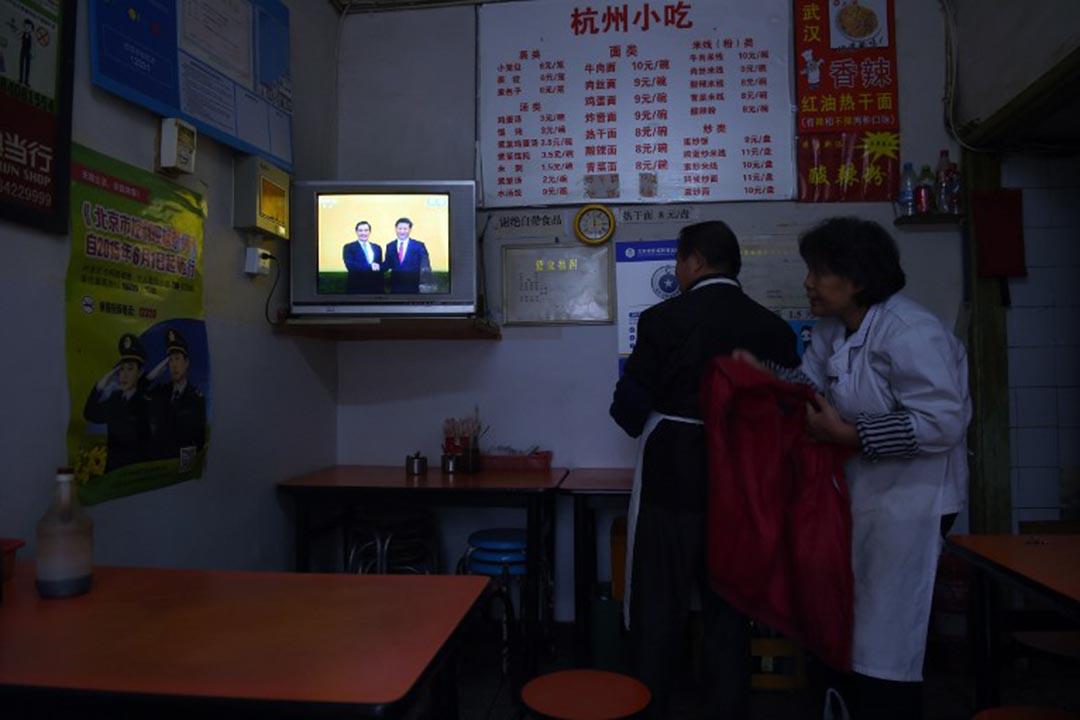 兩名餐廳員工在觀看習馬大會的直播。攝 : Greg Baker/AFP