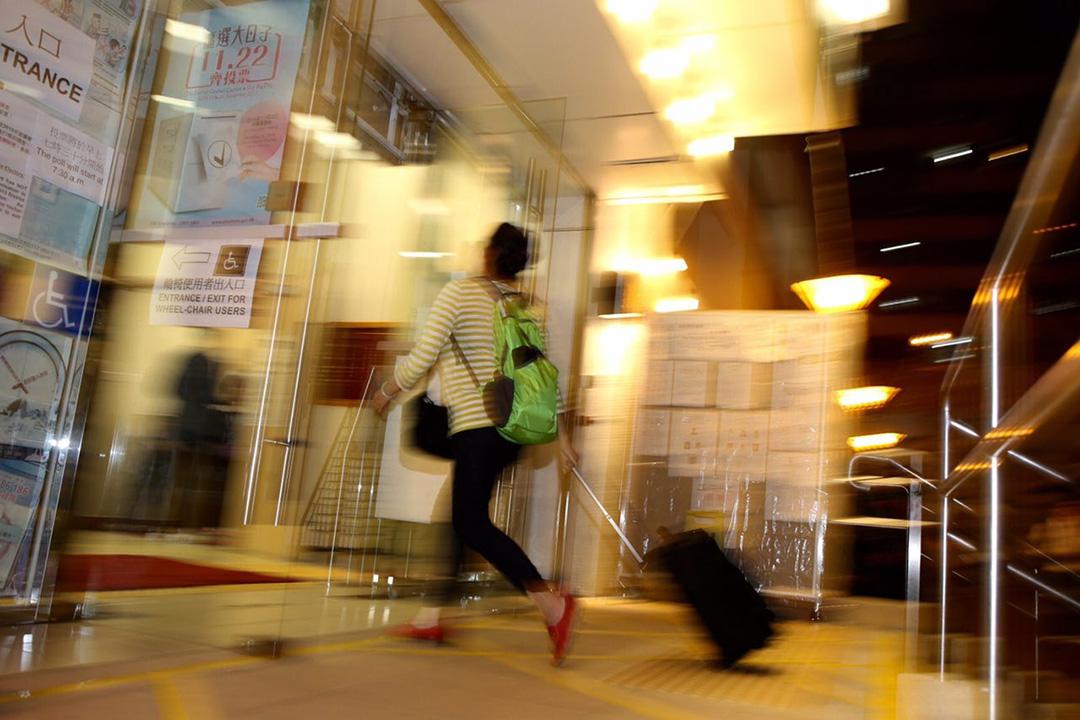 長沙灣麗閣,有帶行李喼的市民趕在10時半票站關門前投票。攝:羅國輝/端傳媒