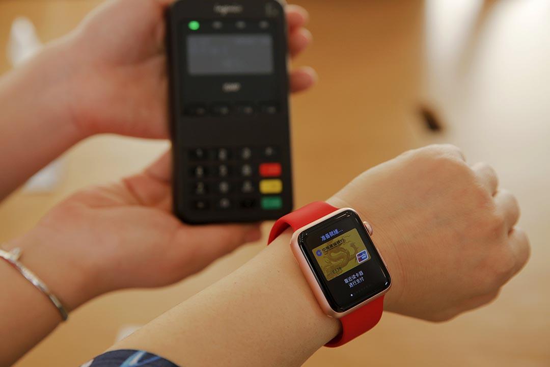 2月17日,北京蘋果旗艦店內,店員示範如何使用 Apple Pay 付款。攝:Damir Sagol/jREUTERS
