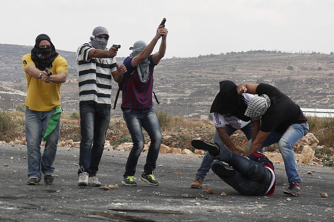 2015年10月7日,約旦河西岸拉姆安拉附近,裝扮成示威者的以色列軍警拘捕一名巴勒斯坦示威者。攝:ABBAS MOMAN/IAFP