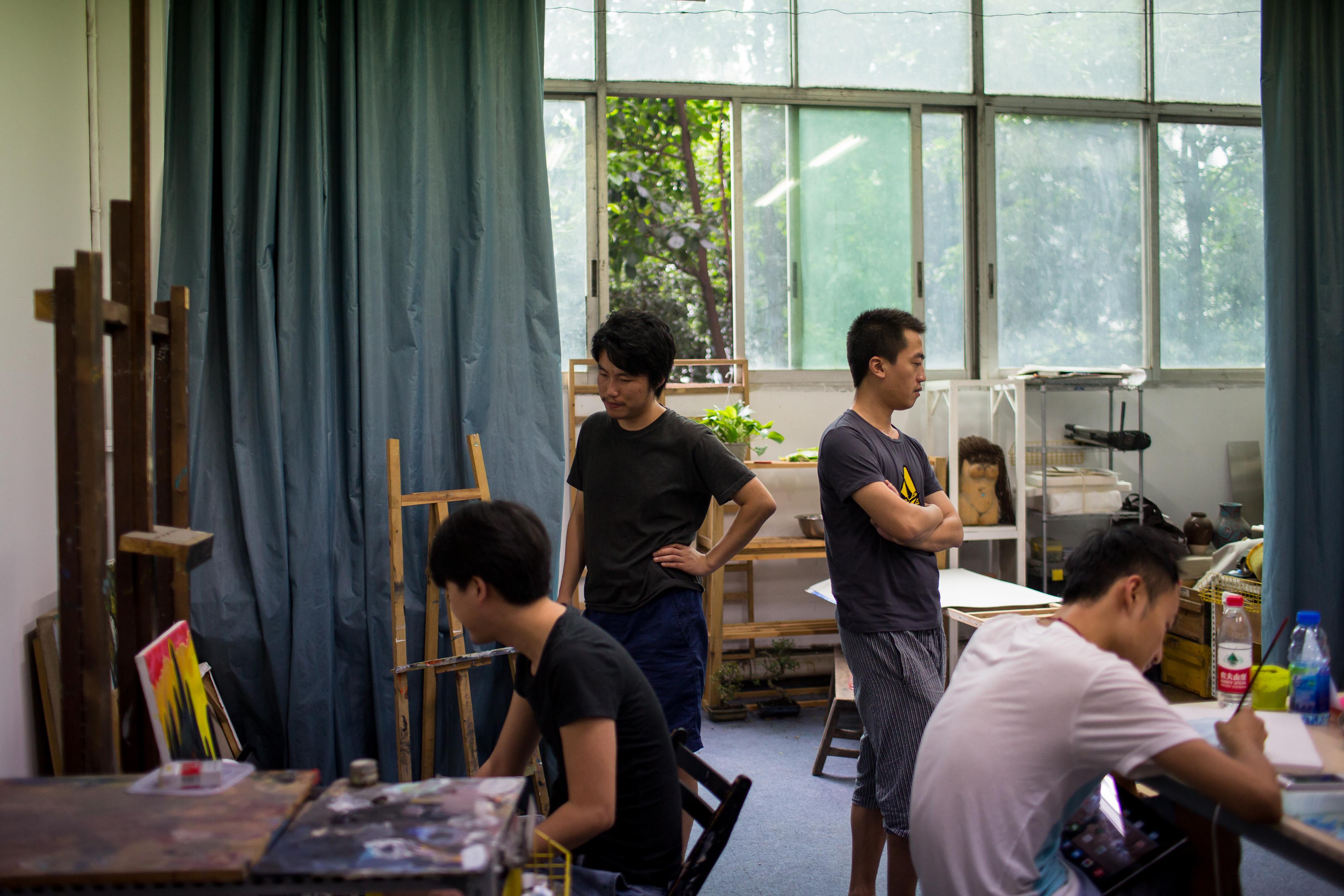 劉偉偉(左二)在朋友的油畫工作室。攝: Billy H.C. Kwok/ 端傳媒