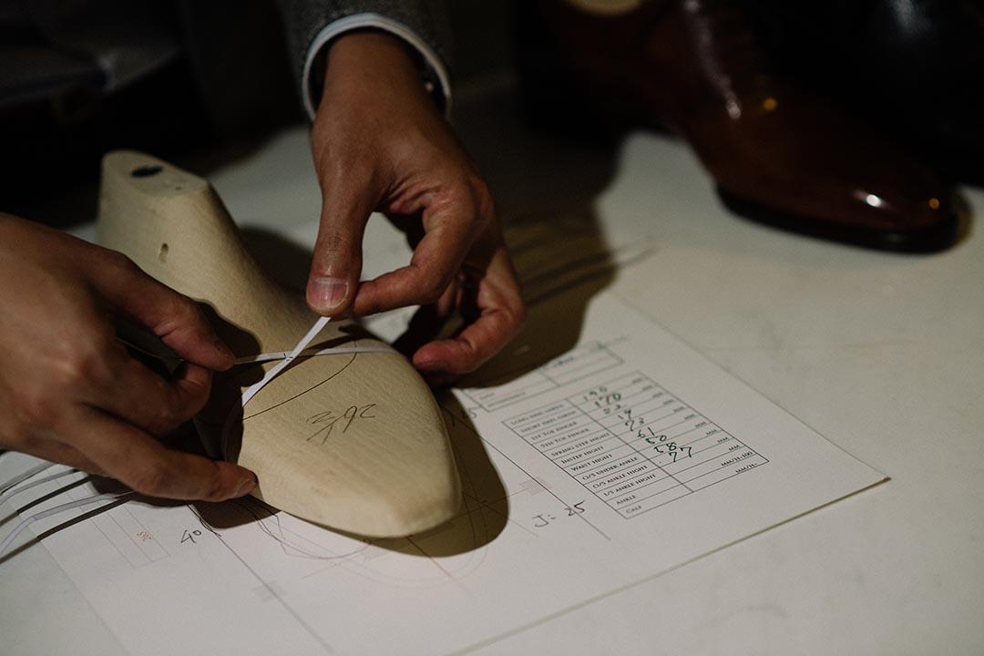 Okuyama 以鞋楦作示範,他平日就是這樣以紙條,全方位量度客人雙腳的尺寸。 攝:LIT MA/端傳媒