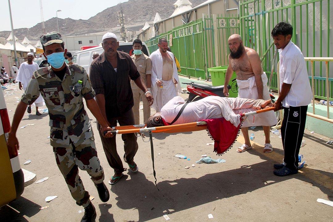 朝聖者和沙特急救人員合力抬送躺在擔架上的女子往醫院。攝 : AFP