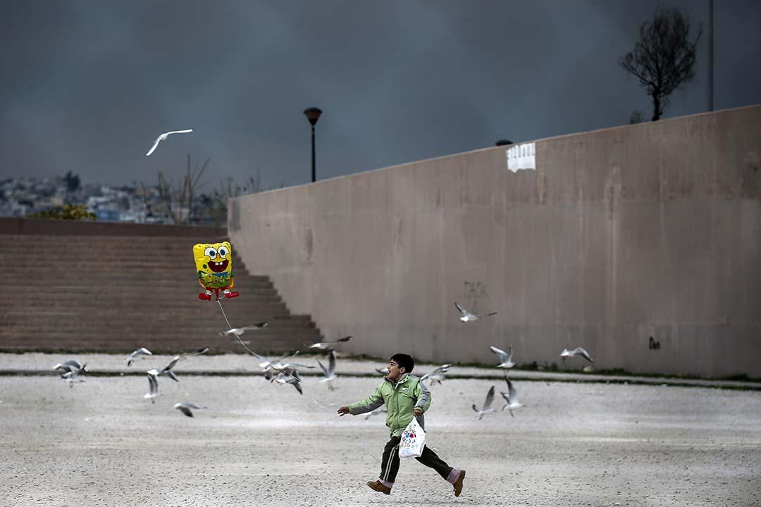 2015年12月16日,希臘,一名難民男童在雅典郊區的運動場外手持汽球嬉戲。攝:Alkis Konstantinidis/REUTERS