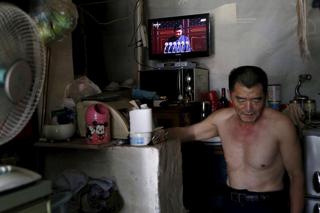 一名男人在他北京經營的士多𥚃,電視播放習近平出席閱兵儀式。