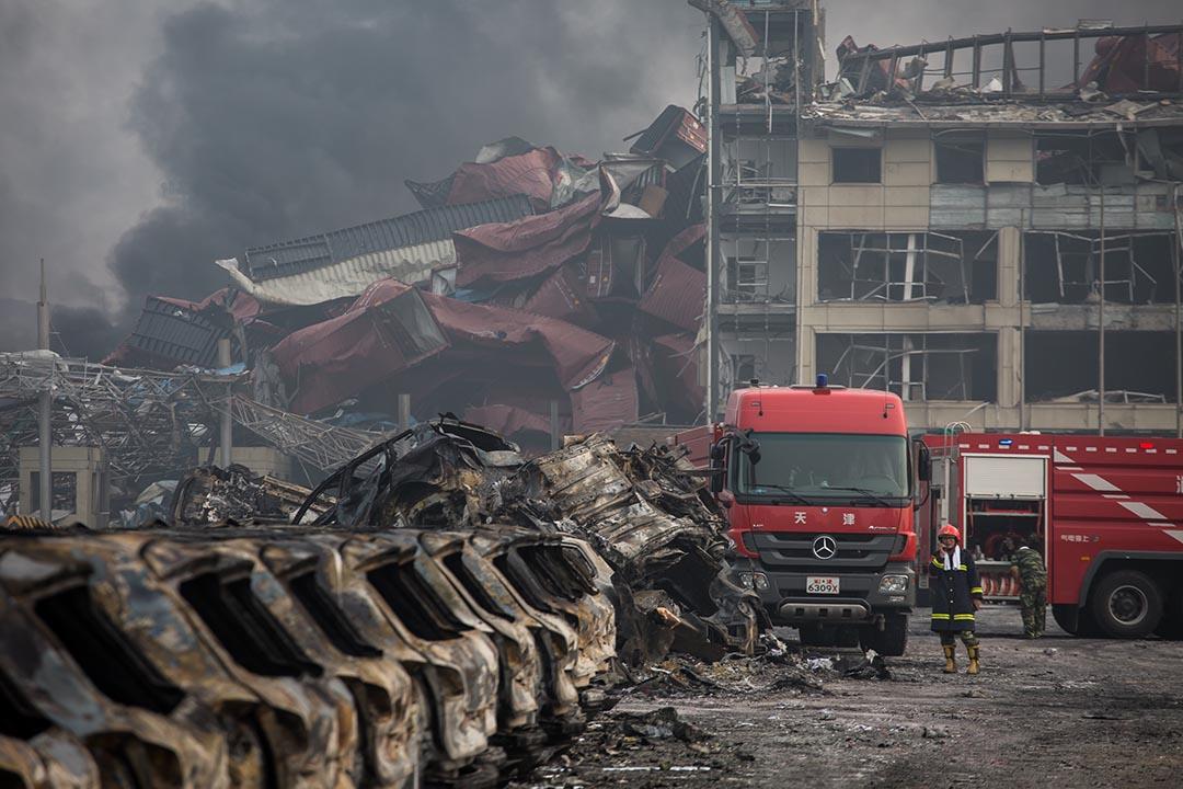 2015年8月14日,天津,消防員在爆炸現場的房車殘骸旁邊戒備。攝:Billy H.C. Kwok/端傳媒