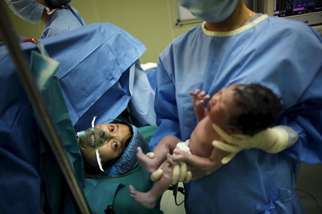 上海一間醫院,一名女子剖腹產後看着她的孩子。攝:Carlos Barria/REUTERS