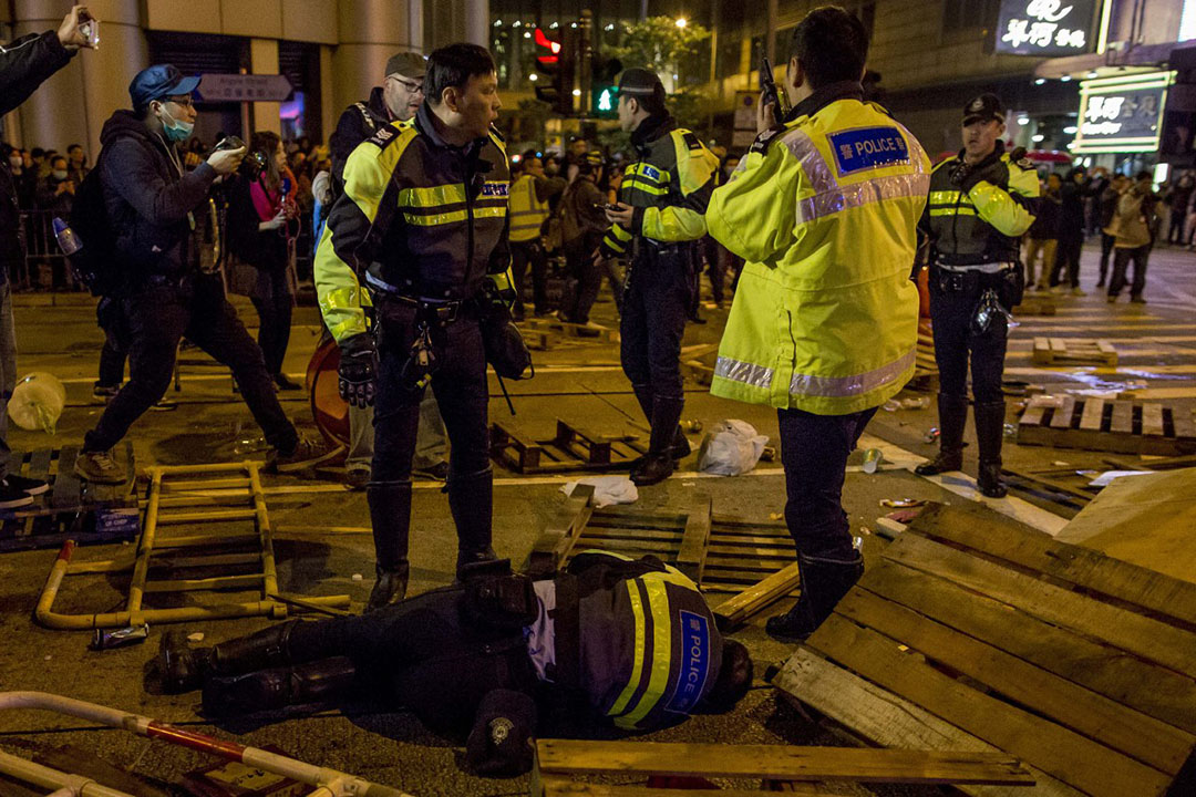2016年2月9日凌晨,旺角,一名警察在亞皆老街倒地。攝:Billy H.C. Kwok/端傳媒