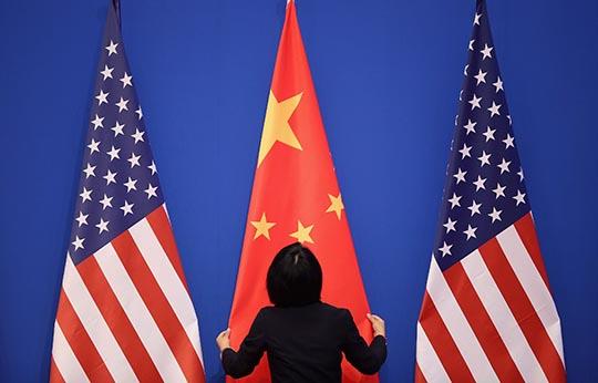 2014年7月9日,北京釣魚台國賓館,中美雙方舉行戰略與經濟合作對話前,工作人員整理場地的中美國旗。攝:Feng Li/GETTY