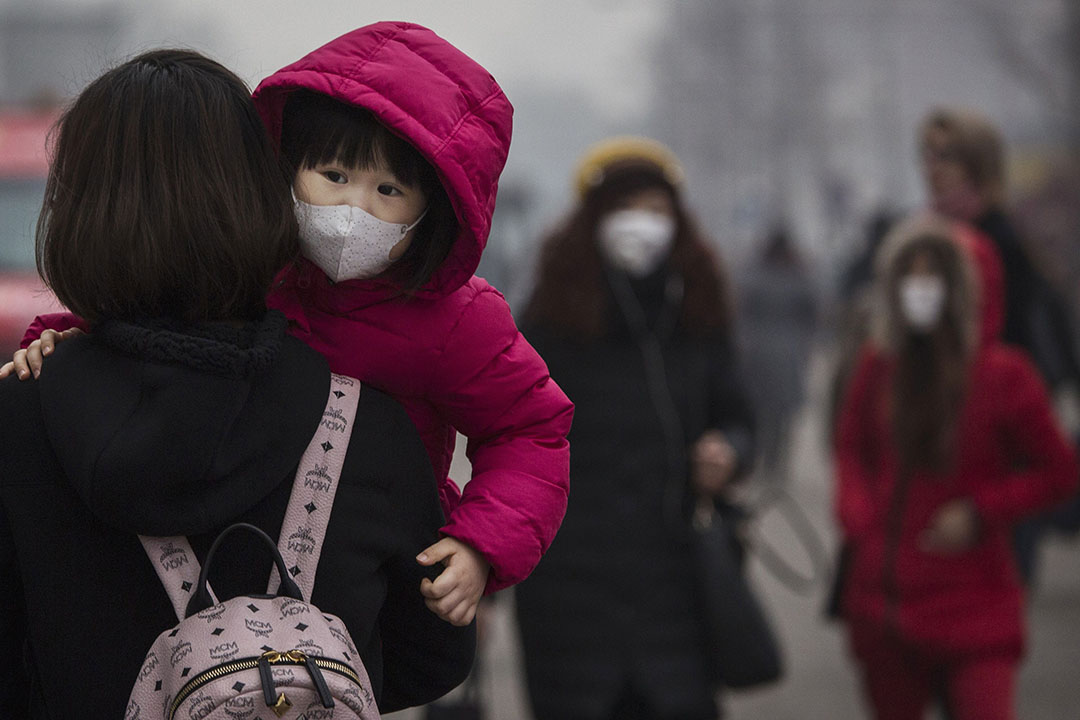 2015年12月8日,北京,一名女童在嚴重霧霾下戴口罩上街。攝:Kevin Frayer/GETTY