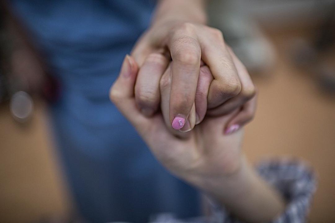 隆下巴手術結束後,緊緊抓住其中一名陪同朋友的手,在手術台上哭泣。而醫生稱她的整個整容過程至今才進行了一半。攝: 馮海泳