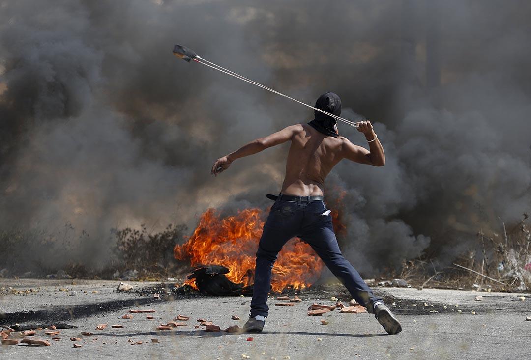 2015年10月5日 約旦河西岸 巴勒斯坦示威者用繩索向以色列軍隊投擲石塊。攝:Mohamad Torokman/ Reuters