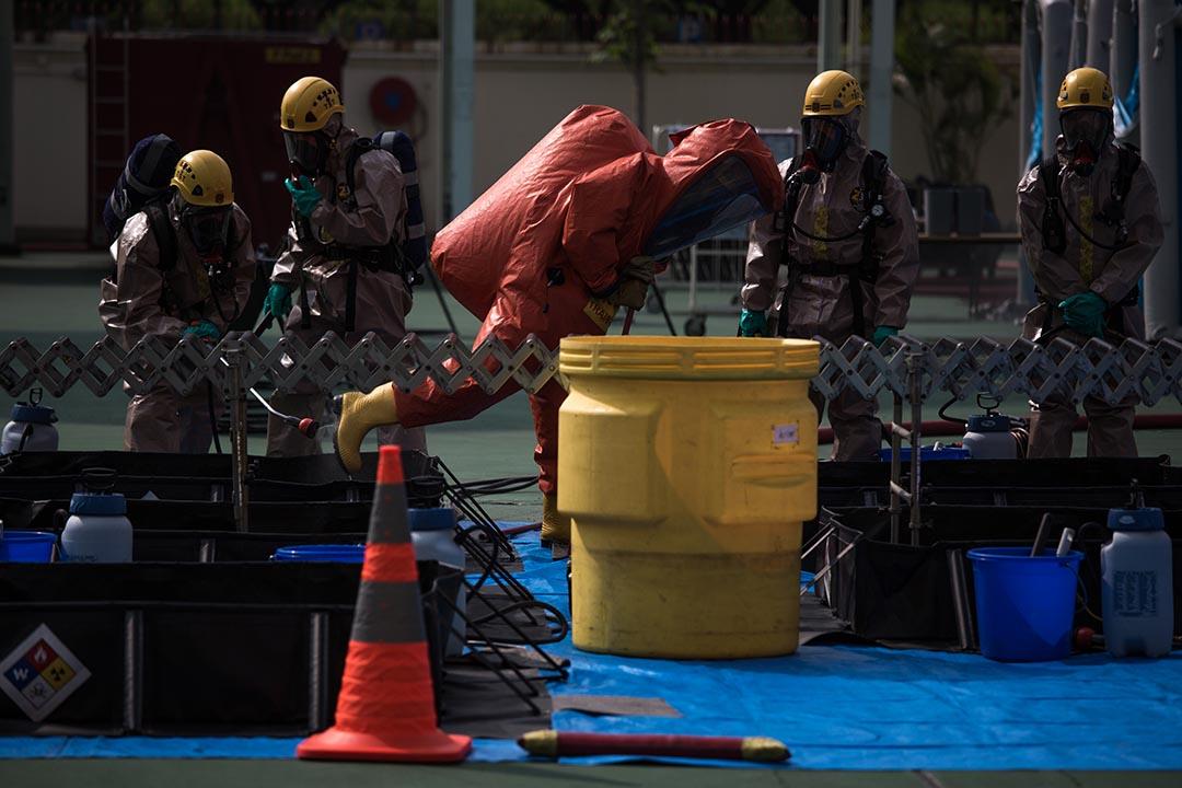 負責處理危害物質的 EVO 化學保護袍消防人員在暖區接受清洗程序。攝:盧翊銘/端傳媒
