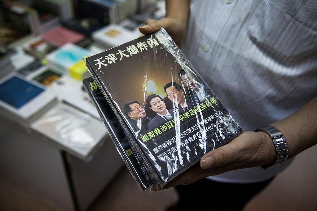 2015年11月8日,端傳媒記者採訪仍有營業的香港銅鑼灣書店,店員展示一本有關天津爆炸的禁書。攝:Billy H.C. Kwok/端傳媒