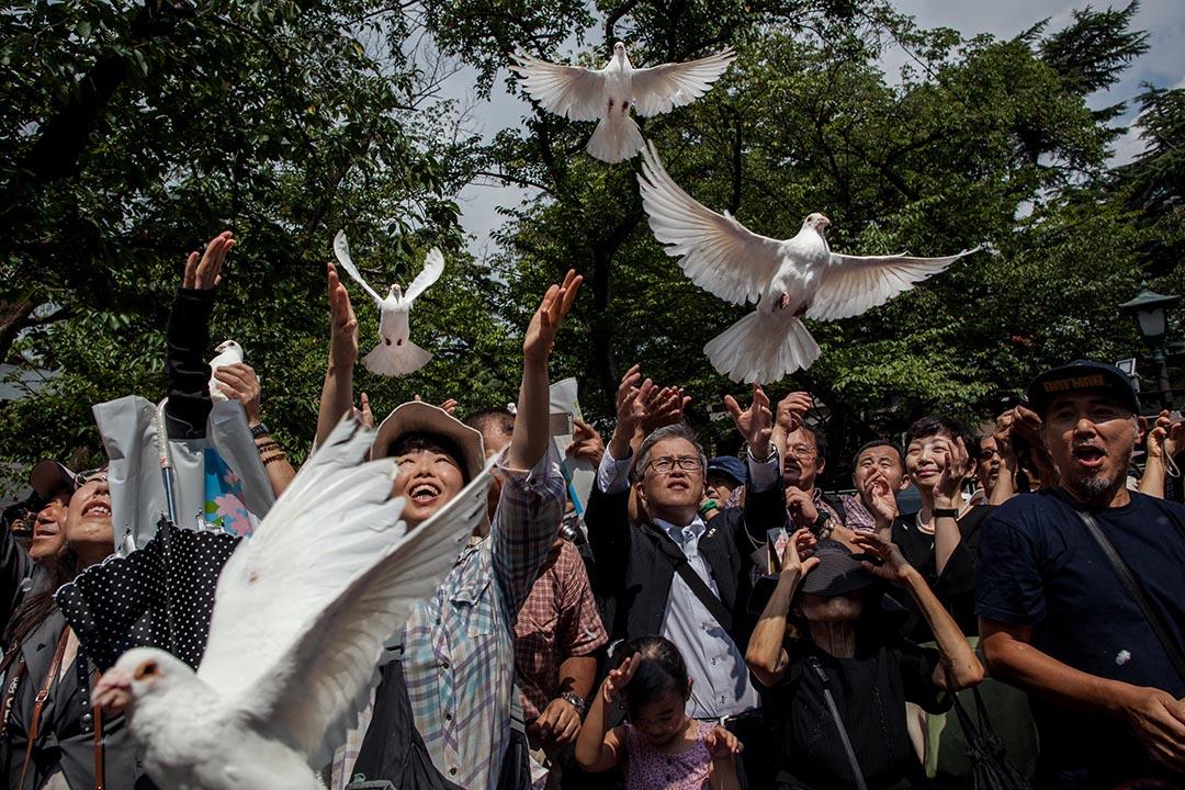日本市民在靖國神社放飛幾十隻鴿子,記念二戰投降70週年。攝 : Nicole Tung/端傳媒