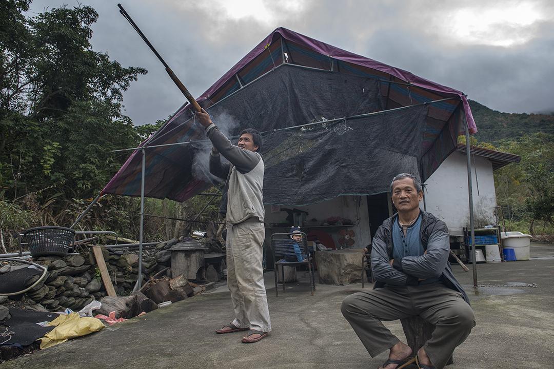 Talum Dusuluman(王光祿)和他的姪子。姪兒正在展示土製獵槍的使用方式。攝:Alberto Buzzola/端傳媒