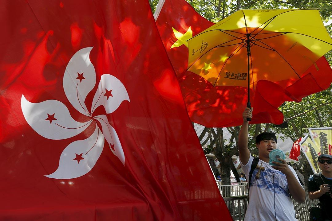 2015年6月7日香港泛民主派發起落區行動宣傳反對假普選,一名手持黃傘的泛民人士被親中人士以中國國旗和香港區旗阻擋。 攝:Bobby Yip/REUTERS