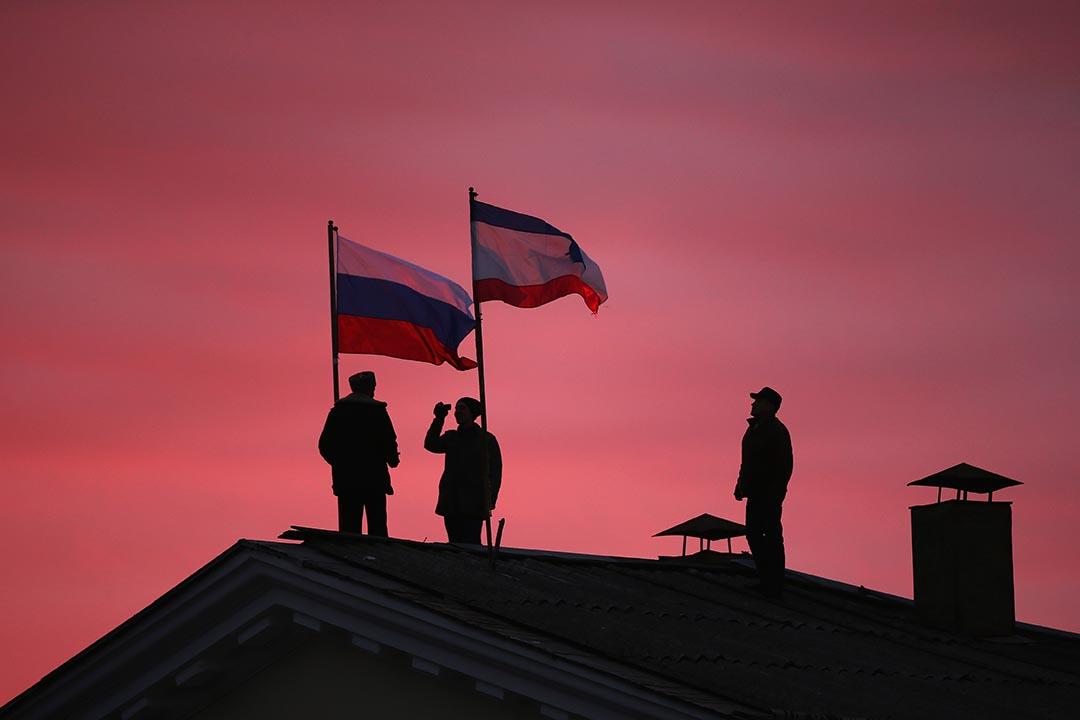 2014年3月17日,克里米亞巴赫奇薩賴,哥薩克人在市政廳樓頂插上俄羅斯和克里米亞國旗。攝:Dan Kitwood/Getty Images