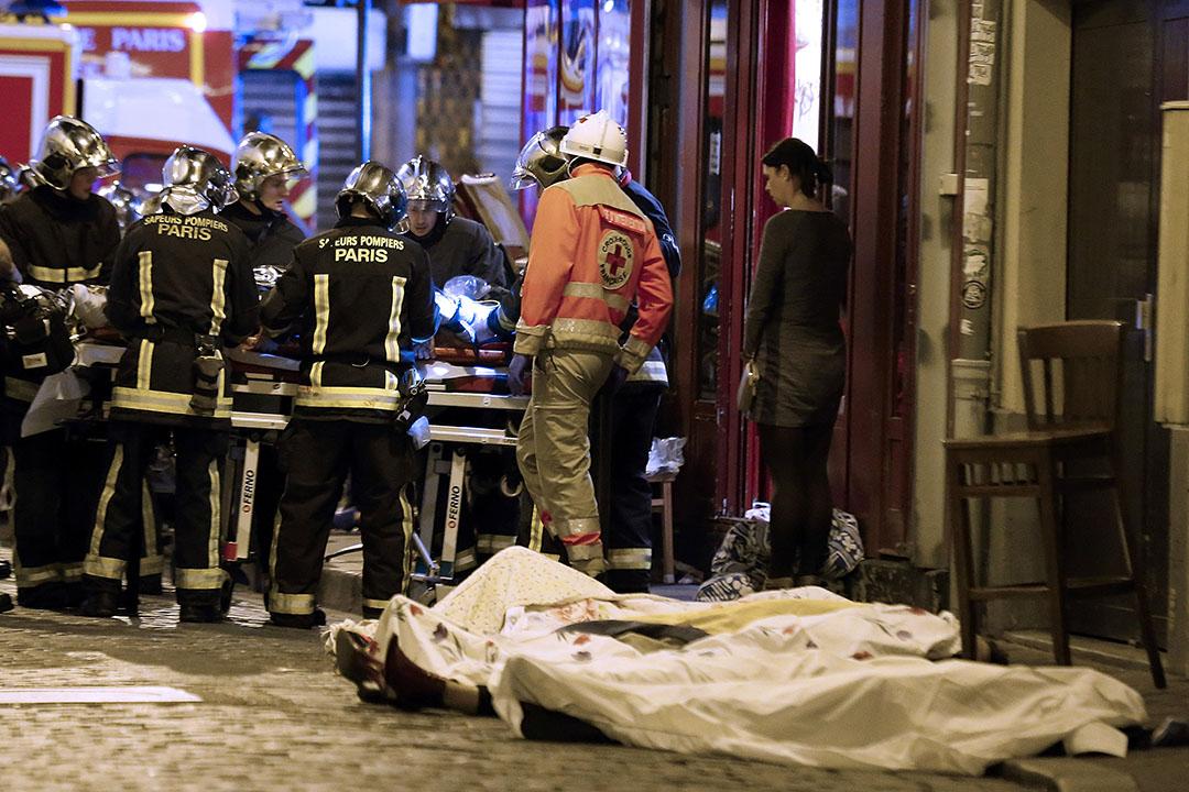 救援人員在巴黎十區的一間餐廳外搶救傷者,地上放有多具屍體。攝:Jacques Brinon/AP