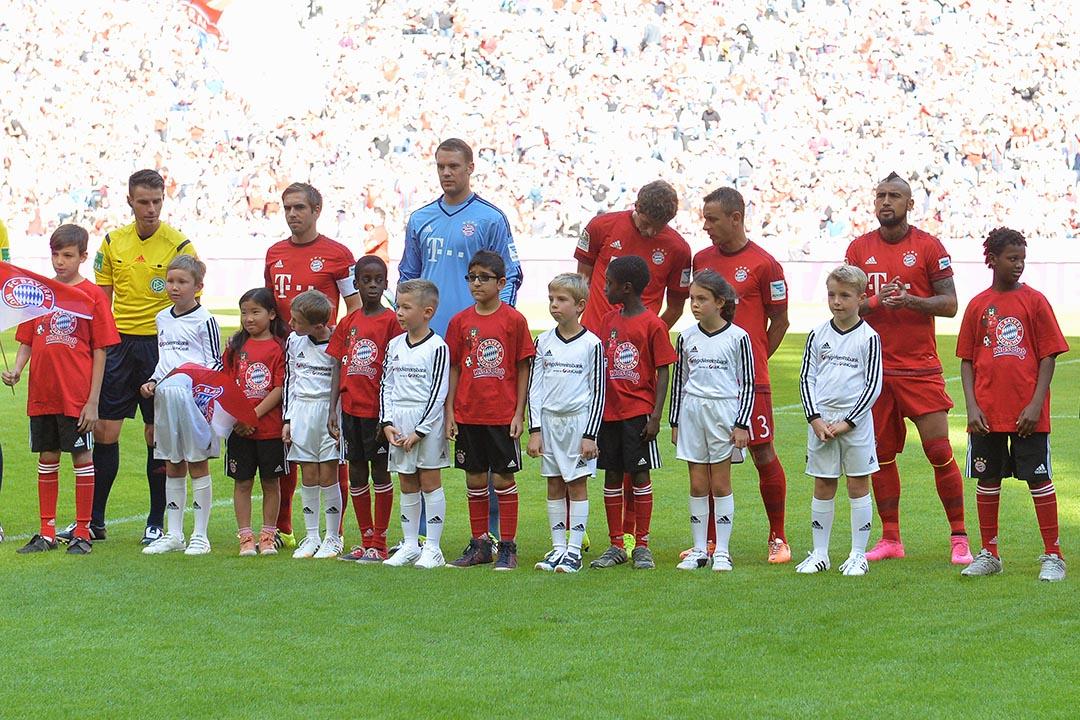 2015年9月12日,德國球隊拜仁慕尼黑的球員於球賽開始前與幾位難民小孩一起進場。攝:Kerstin Joensson/AP