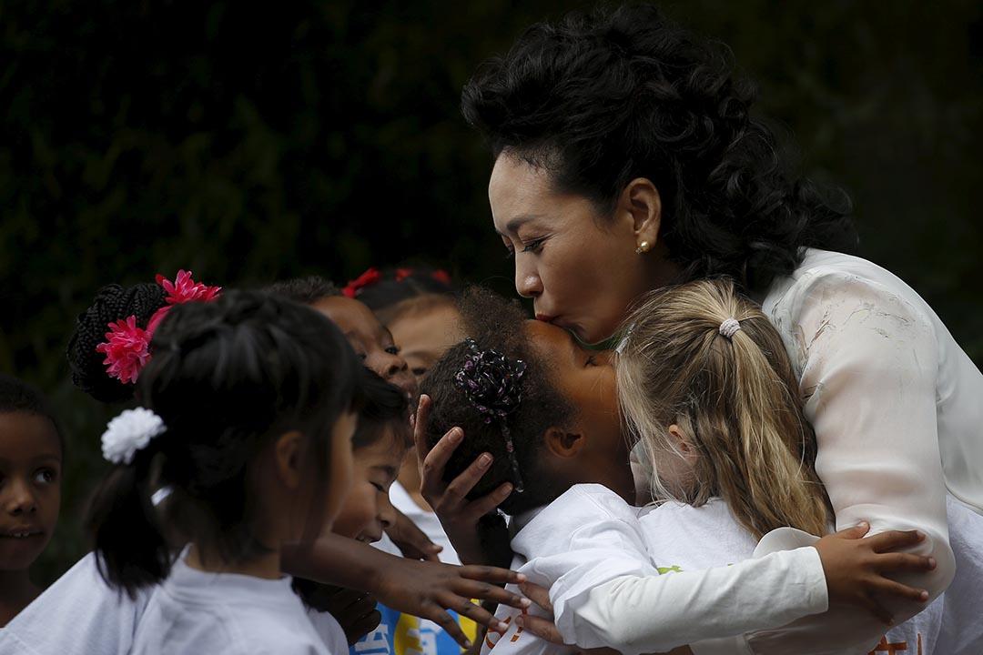 中國第一夫人彭麗媛於訪美期間親吻一名女孩。攝:Carlos Barria/REUTERS