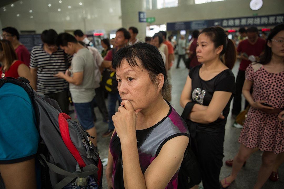 婦女維權人士張玉芬在北京西站購買前往西安的火車票。時常承接取證業務的她,常在全國各地奔波。攝: Jason Jia/端傳媒