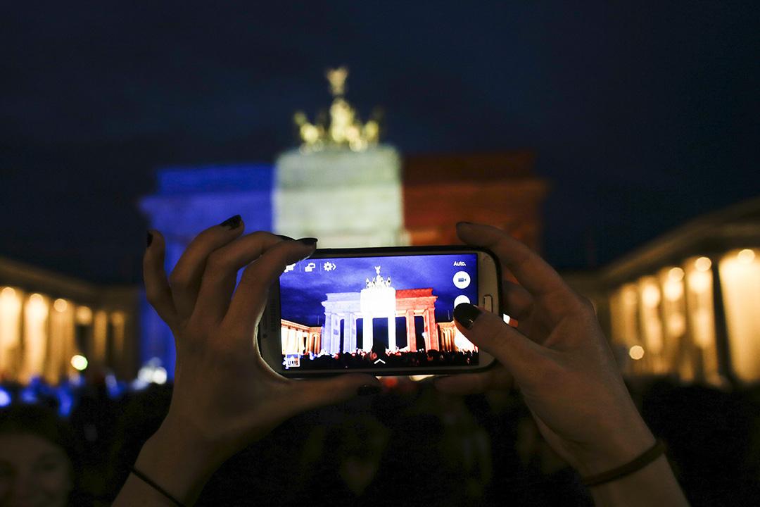 2015年11月14日,德國,勃蘭登堡門在巴黎恐襲後投射了紅白藍三色以示悼念,有悼念人士以手機拍照。攝:Markus Schreiber/AP