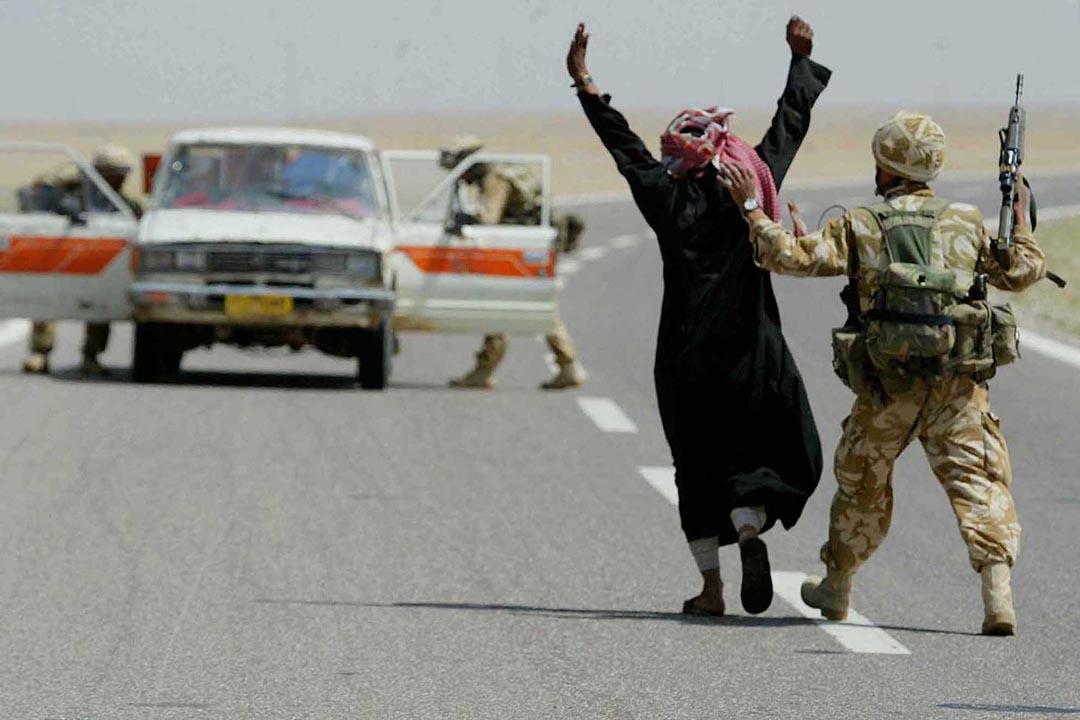 2003年4月1日,伊拉克巴斯拉英國士兵截查幾名伊拉克男子。攝:James Vellacott/POOL/REUTERS