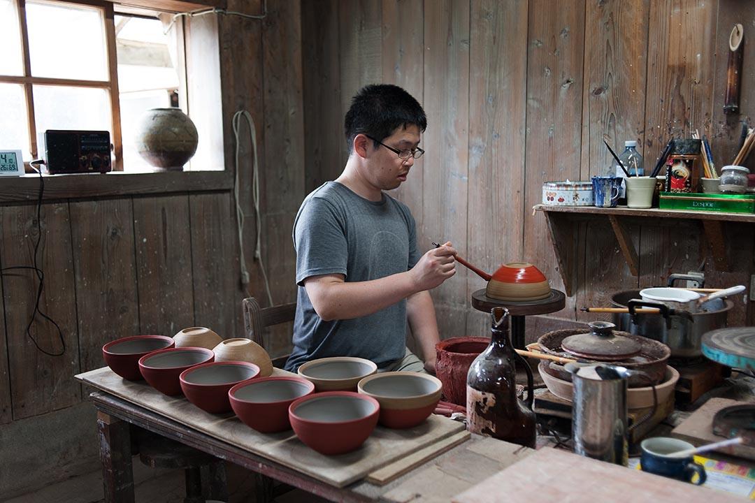 陶工們將釉藥仔細地澆在素燒好的器物之上。(攝:Kentaro Takahashi / 林琪香)